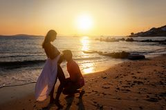 Man kisses the belly of his pregnant wife on a beach. During a romantic sunset royalty free stock photo