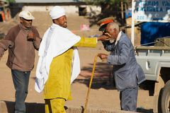 Man kisses cross at the hand of an Orthodox priest at the street in Lalibela, Ethiopia. LALIBELA, ETHIOPIA - JANUARY 27, 2010: Unidentified man kisses cross at stock image