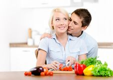 Man kisses girl while she is cooking Stock Images