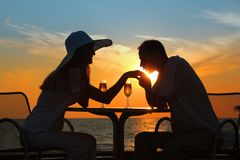 Man kisses hand to woman on sunset outside Stock Image