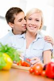 Man kisses pretty female while she is cooking Stock Images