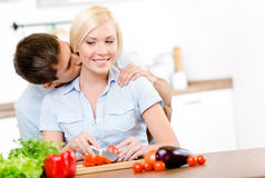 Man kisses pretty woman while she is cooking Royalty Free Stock Photography