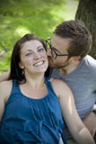 Man kisses woman on cheek. Young men kisses girlfriend on the cheek royalty free stock photo