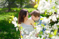 Man kisses a woman's shoulder in a spring garden Royalty Free Stock Photo