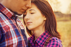 Man kisses a woman, serene scene. Couple in love, men kisses a women with closed eyes, serene scene, image with vintage instagram filter Stock Photos
