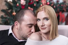 Man kisses a woman in the shoulder. Man kisses a woman in a bare shoulder against the background of a Christmas tree stock photo