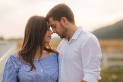 Man kisses a woman in nature. Romantic atmosphere stock images
