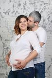 Man kisses young pregnant woman in jeans. Man kisses young pregnant women in jeans in white studio with brick wall stock photos