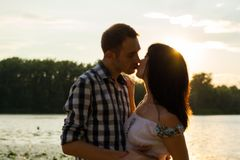The man is kisses the young woman and hugs her at sunset background, blurred. royalty free stock photos