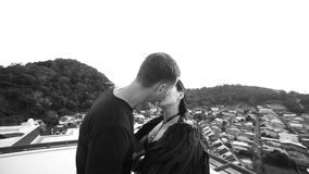 Man kissing black angel woman on the rooftop stock footage