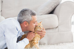 Man kissing cat by sofa at home Stock Photography