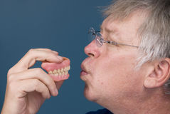 Man kissing dentures Royalty Free Stock Image