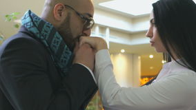 Man kissing the hands of his girlfriend. Stylish man of Arab origin was kissing the hands of his girlfriend in an airport lounge before departure stock video footage