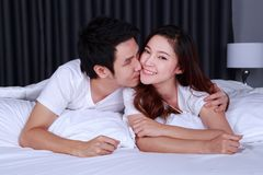 Man is kissing his beautiful smiling wife in cheek on bed Stock Photo