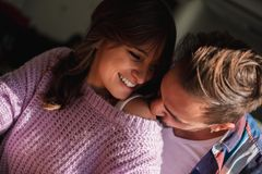 Man kissing his girlfriend`s shoulder while she is smiling. Beautiful sunny day royalty free stock images
