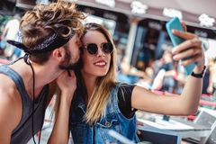 Man kissing his girlfriend while she is taking selfie. In a coffee shop stock photos