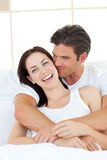 Man kissing his laughing girlfriend in the bedroom Royalty Free Stock Images