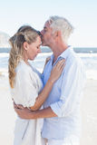 Man kissing his partner on the forehead at the beach Royalty Free Stock Image