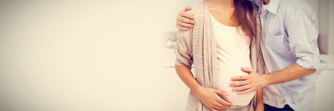 Man kissing his pregnant wife royalty free stock photo