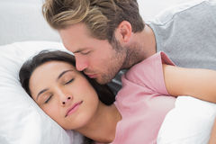 Man kissing his sleeping wife on the cheek Royalty Free Stock Photography