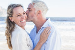 Man kissing his smiling partner on the cheek at the beach Stock Images