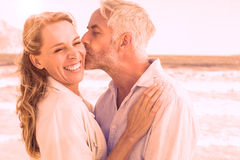 Man kissing his smiling partner on the cheek at the beach Royalty Free Stock Photography