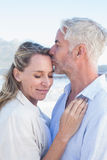 Man kissing his smiling partner on the forehead at the beach Royalty Free Stock Photo