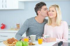 Man kissing partner at breakfast table Stock Image