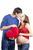 Man kissing pregnant wife nose holding red heart Royalty Free Stock Photos