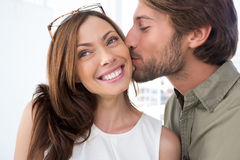 Man kissing pretty woman on the cheek Stock Photo