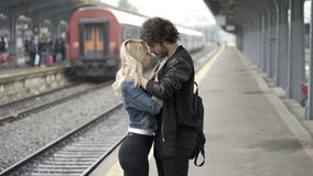 Man kissing and saying and waving goodbye to his girlfriend in train station before leaving stock footage