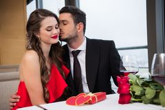 man kissing smiling girlfriend during romantic date in restaurant, st royalty free stock photography