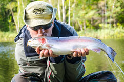 Man kissing trout fish Royalty Free Stock Photography