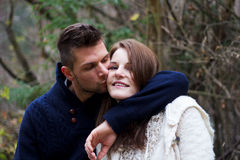 Man kissing woman on the cheek. In the forest in front of trees Stock Photos