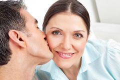 Man kissing woman on cheek. Elderly men kissing his smiling women on the cheek Royalty Free Stock Photography