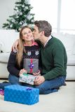 Man Kissing Woman On Cheek With Christmas Gifts Royalty Free Stock Photography