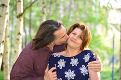 Man kissing a woman on the cheek in  park Royalty Free Stock Photography