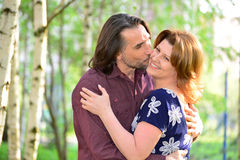 Man kissing a woman on the cheek in  park Stock Image