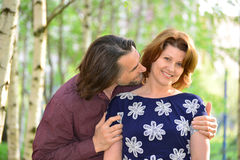 Man kissing a woman on the cheek in  park Stock Images