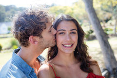 Man kissing woman on cheek. In park on a sunny day Royalty Free Stock Image