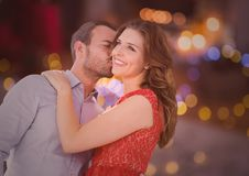 Man kissing woman on cheeks. Against bokeh background Stock Images