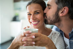 Man kissing woman on cheeks while having coffee. Man kissing women on cheeks while having coffee at home Stock Photography