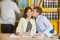 Man Kissing Woman In College Library Stock Photography