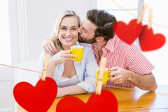 Man kissing a woman. Composite image of red hearts and man kissing a woman Stock Photos