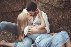 Man kissing a woman in the hayloft. Stock Images