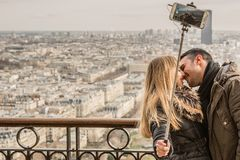 Man Kissing Woman Holding Selfie Stick Royalty Free Stock Images