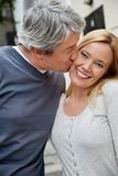 Man Kissing Woman. Middle aged men kissing happy woman Royalty Free Stock Photos