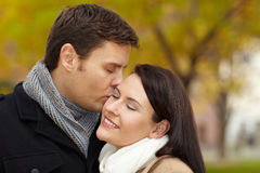 Man kissing woman in park Stock Photos