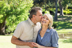 Man kissing woman in park Stock Photography