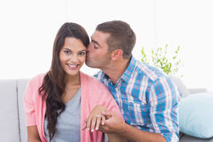 Man kissing woman wearing engagement ring Stock Images